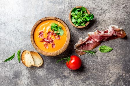 Spanish tomato soup Salmorejo served in olive wooden bowl with ham jamon serrano on stone background. Top view Zdjęcie Seryjne