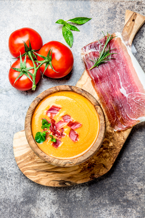 Spanish tomato soup Salmorejo served in olive wooden bowl with ham jamon serrano on stone background. Top view Stock Photo