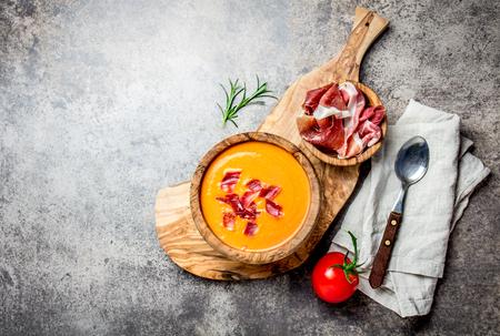 Spaanse tomatensoep Salmorejo geserveerd in olijf houten kom met ham jamón serrano op stenen achtergrond. Bovenaanzicht, kopie ruimte.