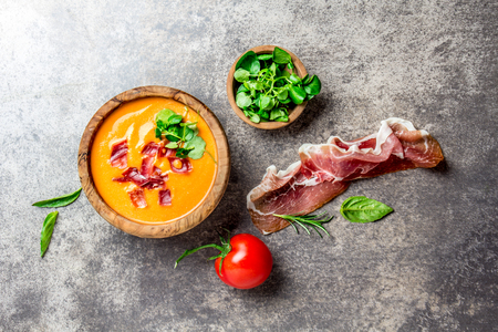 Spanish tomato soup Salmorejo served in olive wooden bowl with ham jamon serrano on stone background. Top view.