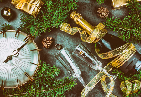 New Year Eve tradition rutual put gold ring to champagne. Spanish and Latin American New year traditions. Two champagne grasses, bottle of champagne, vintage clock and Christmas decorations. Top view Stock Photo