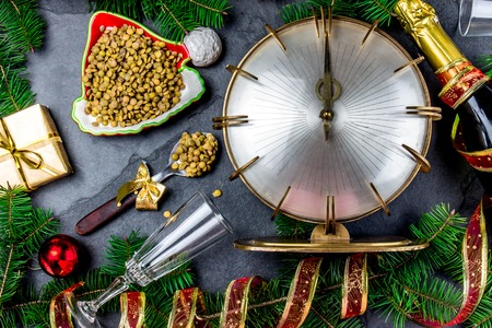 NEW YEARS EVE RITUAL. Tradition to eat spoon of lentil at midnigth. Holidey composition with vintage clock, lentil and Christmas decorations