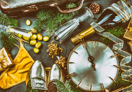 LATIN AMERICAN AND SPANISH NEW YEAR TRADITIONS. empty suitcase, lentil spoon, yellow interior clothes, gold ring in champagne, 12 grapes, money in shoe. Christmas background Stock Photo