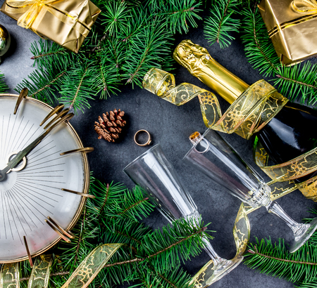 New Year Eve tradition rutual put gold ring to champagne. Spanish and Latin American New year traditions. Two champagne grasses, bottle of champagne, vintage clock and Christmas decorations Top view. Stock Photo