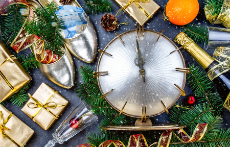 NEW YEAR CELEBRATION. Traditional put money to shoe for have money en New Year. Flat lay composition with vintage clock, shoes with chilean money pesos, champagne, Christmas decorations.