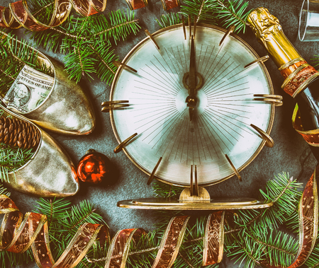 NEW YEAR CELEBRATION. Traditional put money to shoe for have money en New Year. Flat lay composition with vintage clock, shoes with dollars, champagne, Christmas decorations