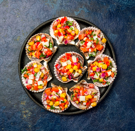 Peruvian style food Scallops a la chalaca. Scallops with onion, tomato, maize, cilantro and lemon on dark blue background. Top view Stock Photo