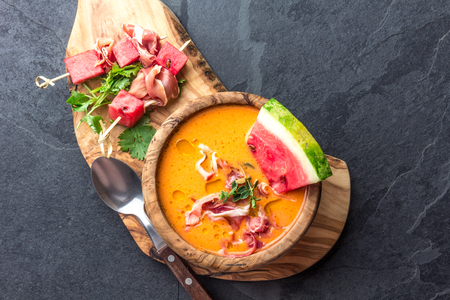 Salmorejo soup with watermelon. Traditional spanish cold tomato soup with watermelon and ham serrano in olive wooden bowl, slate background, top view Standard-Bild