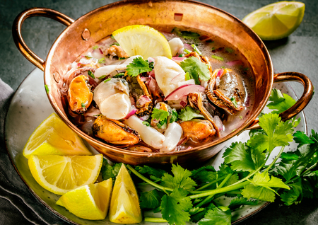 Peruvian Latin American seafood shellfish ceviche cebiche. Raw seafoods - mussels, shrimps, clams, squides marinated in lemon juice with red onion and coriander in cooper bowl, gray slate background Stock Photo