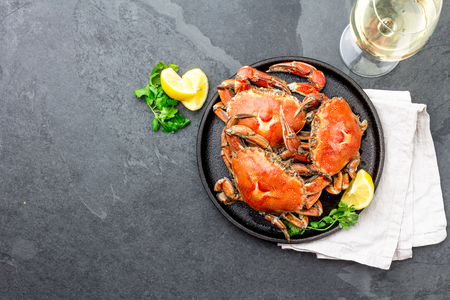 Cooked whole crabs on black plate served with white wine, black slate background, top view