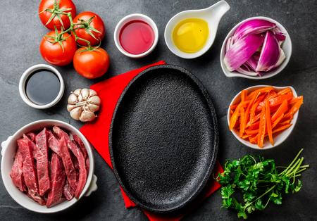 Ingredientes for cooking peruvian dish Lomo saltado - tenderloin beef, yellow chili, tomatoes, onion, oil, soy sauce, vinegar, garlik around black plate