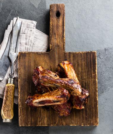 Pork ribs on cutting board, slate background. top view