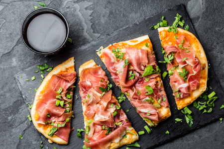 Naan pizza with ham jamon serrano on slate board Stock Photo