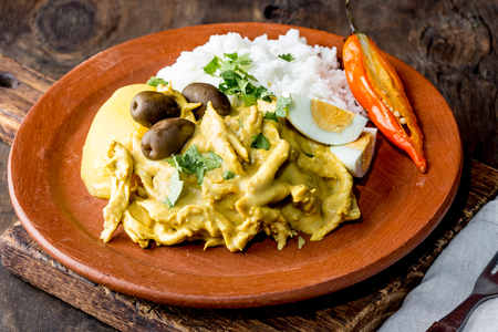 MEXICAN AND PERUVIAN CUISINE. Aji de gallina. Chicken aji de gallina with olives egg and rice on clay plate. Tipical peruvian and mexican dish Stock fotó - 96649747