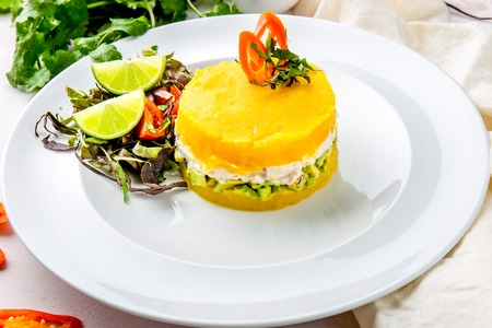 PERUVIAN FOOD. Causa rellena de pollo. Chicken causa rellena. Traditional peruvian dish from yellow potato, chicken, avocado on white plate Foto de archivo - 106488557