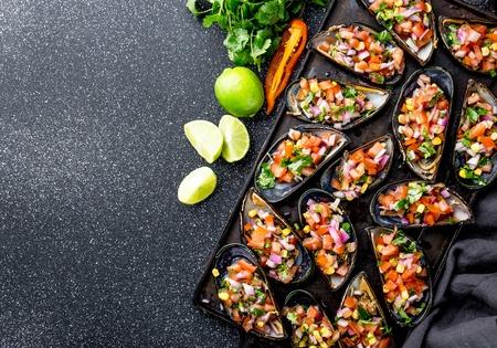 PERUVIAN FOOD. Choros a la chalaca. Big mussels, choros zapatos seasoned with purple onion, tomatoes, corn and lemon. Top view, black background. Traditional peruvian dish Stock Photo