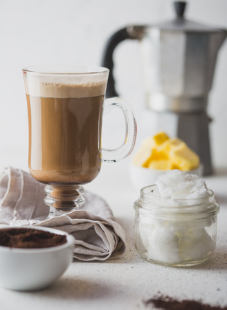 BULLETPROOF COFFEE. Ketogenic keto diet coffe blended with coconut oil and butter. Cup of bulletproof coffee and ingredients on white background.