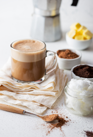 KETOGENIC KETO DIET DRINK. Coffe and cacao blended with coconut oil. Cup of bulletproof coffe with cacao and ingredients on white background. Stock Photo