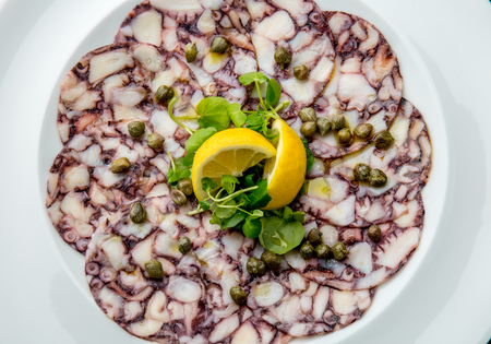 OCTOPUS CARPACCIO. Seafood Raw octopus slices with olive oil, lemon and capers on white plate. Top view. Gray stone background. Stock fotó