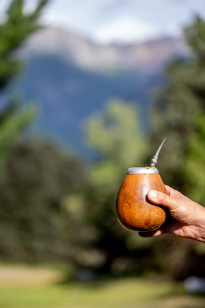 Man holding calabash yerba mate in nature. Travel and adventure concept. Latin American drink yerba mate 免版税图像