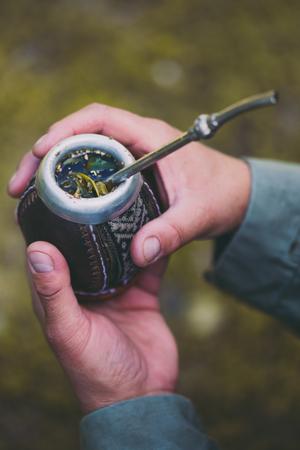 Mann, der Yerba-Kumpel in der Natur hält. Reise- und Abenteuerkonzept. Lateinamerikanisches Getränk Yerba Mate