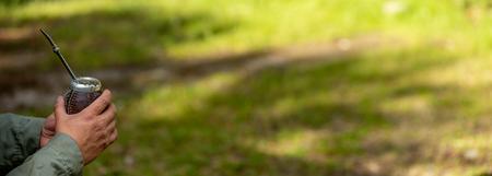 Mann mittleren Alters, der Yerba Mate in der Natur trinkt. Reise- und Abenteuerkonzept. Lateinamerikanisches Getränk Yerba Mate Standard-Bild