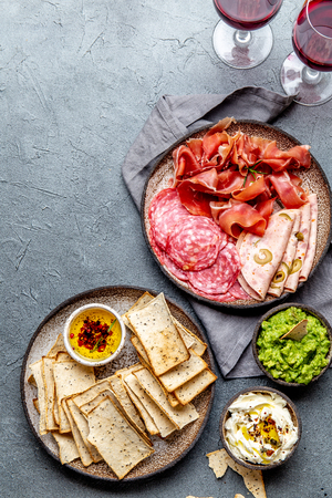 Antipasto. Meat platter, chips and sauces, red wine on gray background. Top view Stock Photo