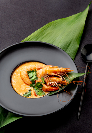 Seafood Soup decorated with whole shrimps and tropical leaves on black plate, black background Banco de Imagens