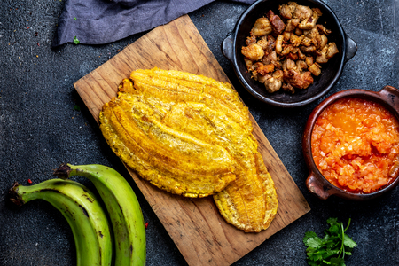 COLOMBIAN CARIBBEAN CENTRAL AMERICAN FOOD. Patacon or toston, fried and flattened whole green plantain banana on white plate. Black background, top view