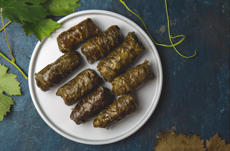 Greek dolmadakia. Rice and meat wrapped in grape leaves. White plate, Blue background