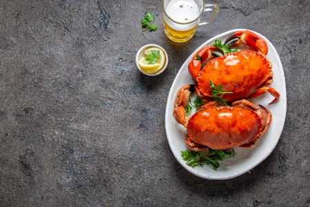 Whole cooked  crabs on white plate with lemon and beer. Gray concrete background. Top view Фото со стока - 116931853
