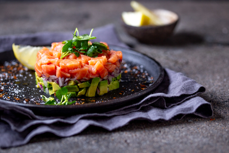 Raw salmon, avocado purple onion salad served in culinary ring on black plate. Black concrete background Reklamní fotografie