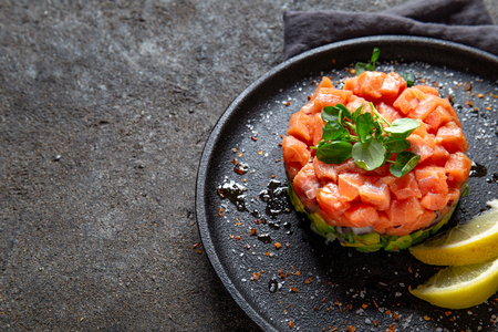 Raw salmon, avocado purple onion salad served in culinary ring on black plate. Black concrete background Фото со стока