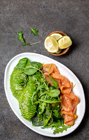Low carbs salad. Spinach, rucola salad with avocado and salmon. Black concrete background, top view.