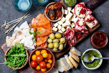 Antipasto. Voorgerecht wijnset. Ham serrano, gerookte zalm, gedroogde en verse tomaten olijven kaas, wijn aan boord. Bovenaanzicht, grijze betonnen achtergrond