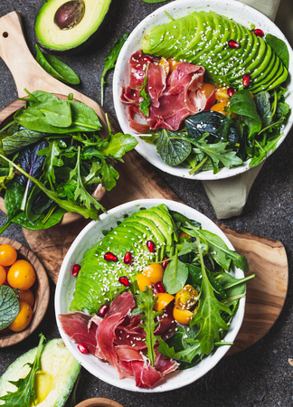 Low carbs bowl. Fresh salad with green spinach, rucola, avocado an ham serrano in white bowl, gray background, top view. Reklamní fotografie