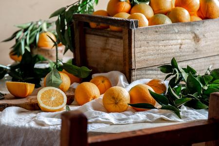 Table with box of fresh orange with orange tree branch and fresh orange juice.