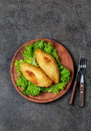 PERUVIAN CHILEAN traditional dish PAPA RELLENA meat stuffed mashed potato on wooden plate.