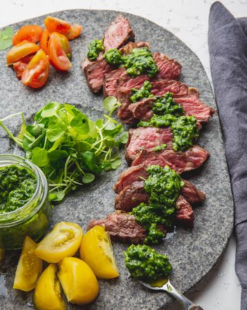 Slices of beef steak with chimmichuri sauce on gray stone plate