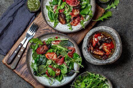Salad with arugula, spinach, dried tomato and ham serrano paleta iberica. Low carbs keto recipe. Stockfoto