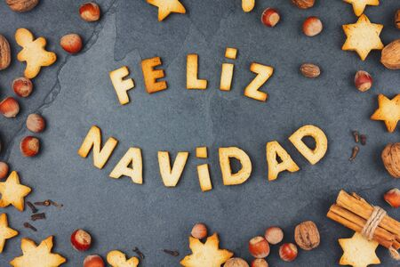 FELIZ NAVIDAD COOKIES. Words Merry Christmas en Spanish with baked cookies, Christmas decoration and nuts on black slate background. Christmas card for hispanic countries top view Reklamní fotografie