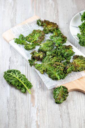 Homemade Green Kale Chips on vintage newspapper, white background Zdjęcie Seryjne