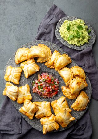 Different little cocktail EMPANADAS on stone plate with tomato sauce and guacamole . Gray background. Latin American and Spanish tipical food.