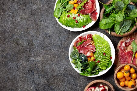 Low carbs bowl. Fresh salad with green spinach, rucola, avocado an ham serrano in white bowl, gray background, top view. Stock Photo