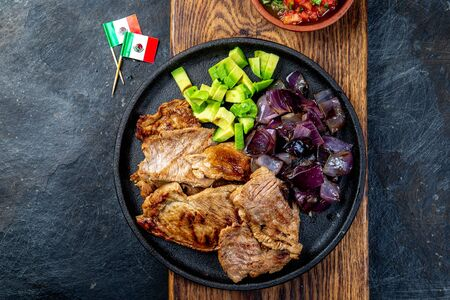 Yucatan Mexican Food Pork chuck. Pork marinaded in orange juice served with avocado, purple onion and rustic tomato sauce Archivio Fotografico