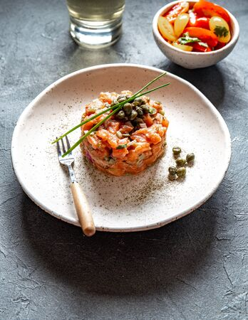 SALMON TARTAR with capers and purple onion on white plate, gray background. 스톡 콘텐츠