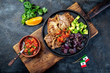 Yucatan Mexican Food Pork chuck. Pork marinaded in orange juice served with avocado, purple onion and rustic tomato sauce