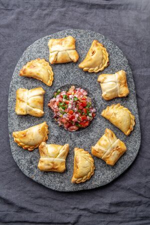 Different little cocktail EMPANADAS on stone plate with tomato sauce and guacamole . Gray background. Latin American and Spanish typical food.