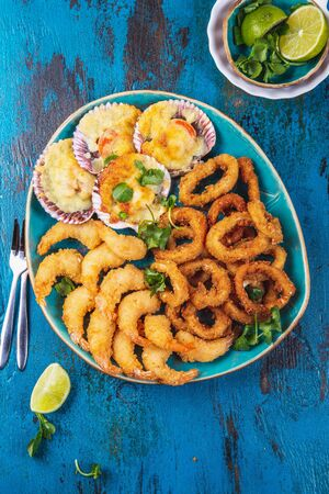 SEAFOOD hot platter baked scallops, fried squid rings and shrimps Stock Photo
