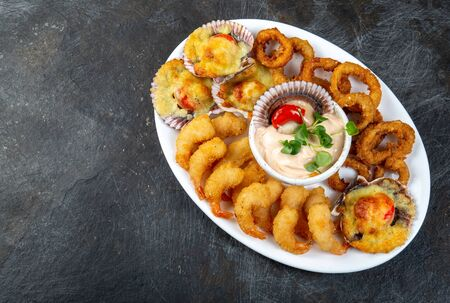 PERUVIAN FOOD. Piqueo caliente. Hot seafood platter fried shrimps, squid rings and baked scallops with sauce